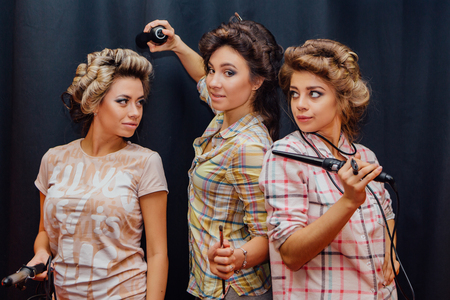 elegancy: Portrait of three young girls making hairdress to each other