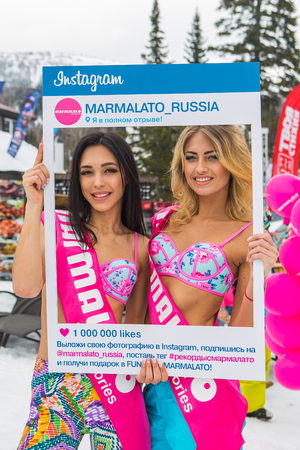 fashon: Sheregesh, Kemerovo region, Russia - April 16, 2016: Grelka Fest is a sports and entertainment activity for ski and snowboard riders in bikini. Beautiful women in colorful bikini with Marmalato instagram frame.