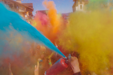 Sheregesh, Kemerovo region, Russia - April 22, 2017: Grelka Fest is a sports and entertainment activity for ski and snowboard riders in bikini. A group of a young people throwing colorful holi powder.