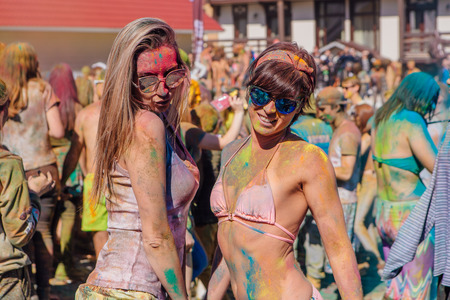vibe: Sheregesh, Kemerovo region, Russia - April 22, 2017: Grelka Fest is a sports and entertainment activity for ski and snowboard riders in bikini. A group of a young people throwing colorful holi powder.