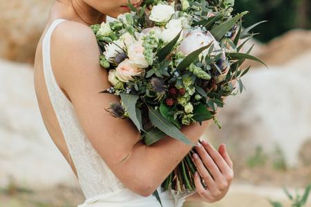 Mooi huwelijksboeket in de handen van de bruid