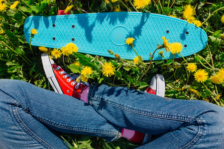 Bright and colorful skateboard and female feet in red sneakers on the grass