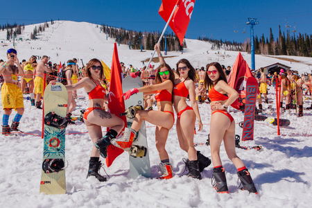 Sheregesh, Kemerovo region, Russia - April 22, 2017: Grelka Fest is a sports and entertainment activity for ski and snowboard riders in bikini in Russia, Sheregesh. Group of young happy pretty women on a snowboard in colorful bikini with flags.