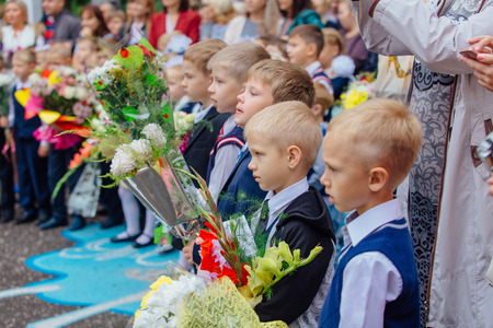 sep: NOVOKUZNETSK, KEMEROVO REGION, RUSSIA - SEP, 1, 2017: Meeting with the first-grade pupils and teacher at schoolyard. The day of knowledge in Russia.