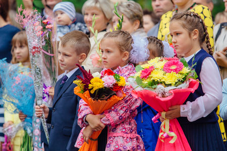 NOVOKUZNETSK, KEMEROVO REGION, RUSSIA - SEP, 1, 2017: Meeting with the first-grade pupils and teacher at schoolyard. The day of knowledge in Russia.