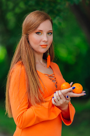 Portrait of pretty red hair woman holding juicy delicious mandarins at summer green park.