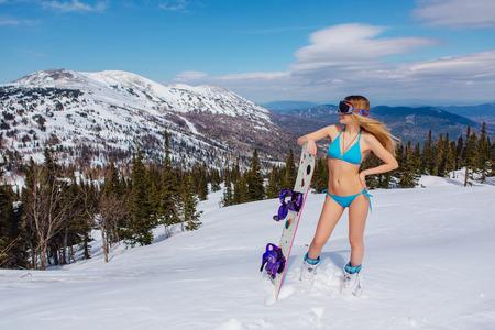 魅力的な若い女性が斜面スノーボードと水着に身を包んだ