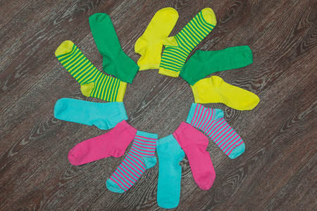 Colorful, bright striped socks on the wooden background in shappe of flower Stock Photo