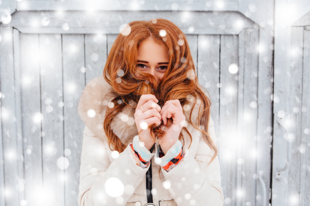 Portrait of a beautiful red hair young woman in warm clothes outdoor on the grey wooden background with fallen snow.