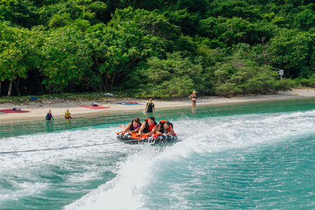 cruising: Chonburi, Thailand - November 26, 2013 :: Tourists on water attraction donut boat during summer vacations Editorial