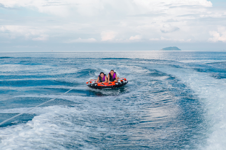 Chonburi, Thailand - November 26, 2013 :: Tourists on water attraction donut boat during summer vacations Editorial