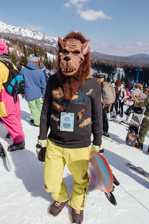Sheregesh, Kemerovo region, Russia - April 22, 2017: Grelka Fest is a sports and entertainment activity for ski and snowboard riders in carnival costume.Young man in carnival costume of werewolf.