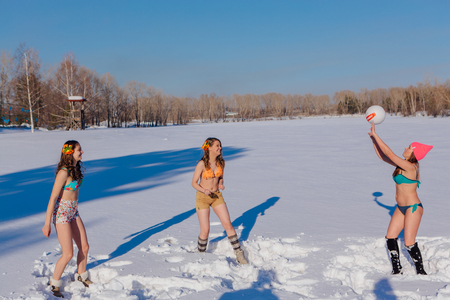 Novokuznetsk, Kemerovo region, Russia-23 Feb, 2017: White beaches of Siberia is an enterteiment activity where people playing beach games dressed in bikini in winter. Women playing volleyball on snow Редакционное