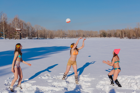 Novokuznetsk, Kemerovo region, Russia-23 Feb, 2017: White beaches of Siberia is an enterteiment activity where people playing beach games dressed in bikini in winter. Women playing volleyball on snow Editorial