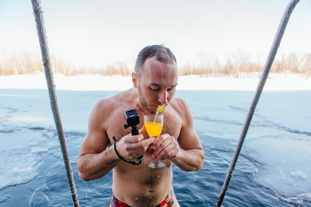 Novokuznetsk, Kemerovo region, Russia - 23 Feb, 2017 : White beaches of Siberia is an enterteiment activity where people playing beach games dressed in bikini in winter. A man swimming in an ice hole Editorial