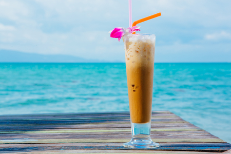 Ice coffee on wooden table with blue sea background 写真素材