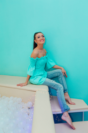 Happy beautiful woman with make up sitting near bright blue wall Foto de archivo