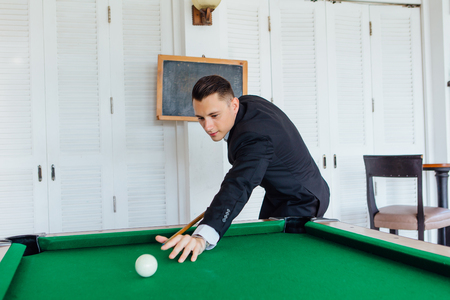 Young handsome man dressed in classic costume playing billiard game alone