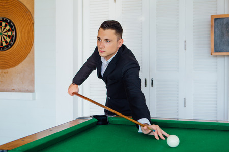 Young handsome man playing billiard game alone 免版税图像