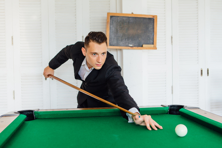 Young handsome man playing billiard game alone Фото со стока