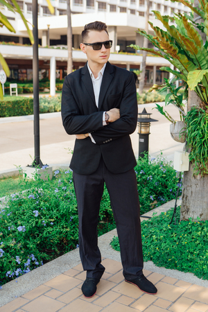 Young stylish handsome man posing in modern city park, wearing suit and sunglasses. Stock Photo