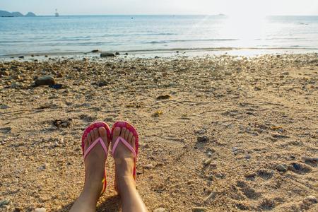 Womans feet on the beach.