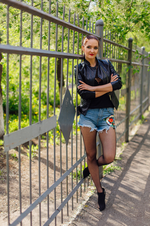 Woman in a leather jacket standing next to an old metal fence