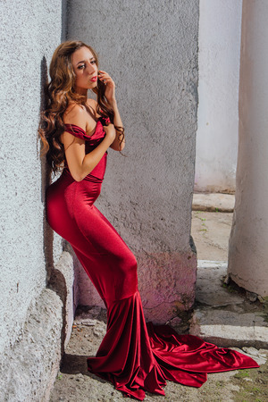 Beautiful young woman in a long red evening gown with a train standing next to the old wall