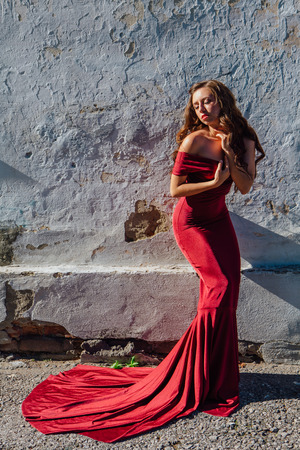 Beautiful young woman in a long red evening gown with a train standing next to the old wall. Copy space Stock Photo