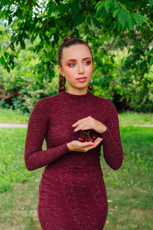 Beautiful young woman with long braid and cherry earrings holding cherry in hands