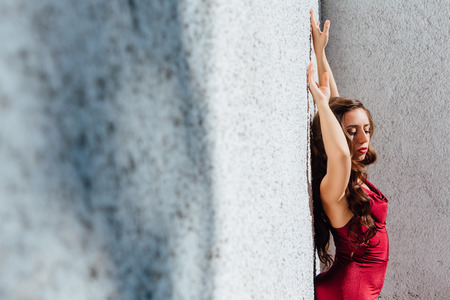 Beautiful young woman in a long red evening gown standing next to the old wall. Copy space. Stock Photo