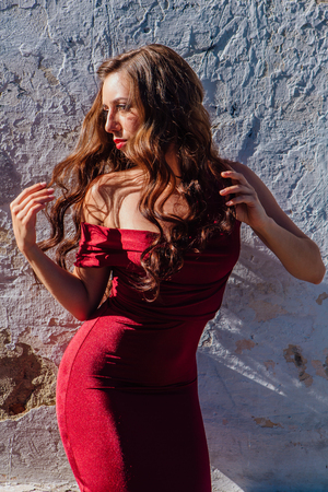 Beautiful young woman in a long red evening gown standing next to the old wall Stock Photo
