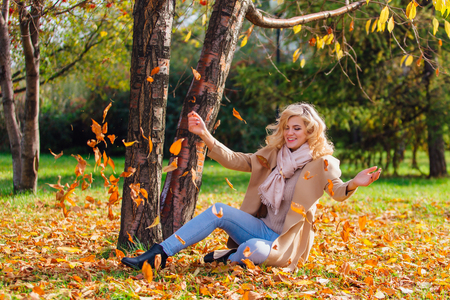 Young beautiful blonde woman throwing up fallen autumn leaves over her head sitting on the ground