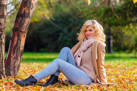 Young beautiful woman sitting under the tree on the ground coverd with fallen yellow autumn leaves