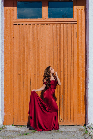 Beautiful young woman in a long red evening gown with a train standing next to the old door
