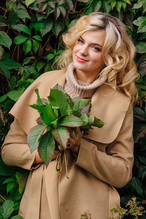 Yuong beautiful woman in sweater and coat stands next to the background of wild grapes holding bouquet of autumn leaves in park Stock Photo
