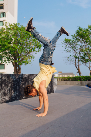 Young handsome man with beard dancing breakdance on the street. Man stands on hands. Stock Photo