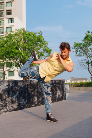 Young handsome man with beard dancing breakdance on the street.