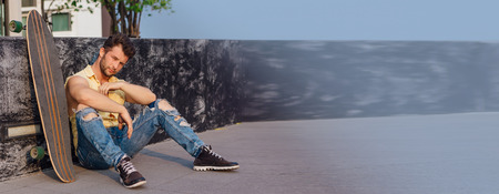 Young handsome man with beard sitting with longboard on the street. Copy space. Stock Photo