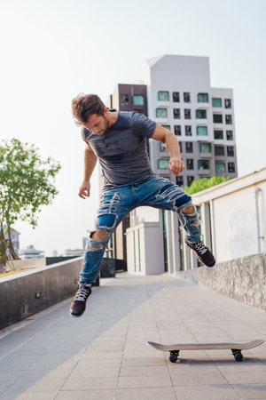 Skateboarder doing a skateboard trick ollie on the street of a city 写真素材