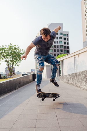 Skateboarder doing a skateboard trick ollie on the street of a city Stock Photo