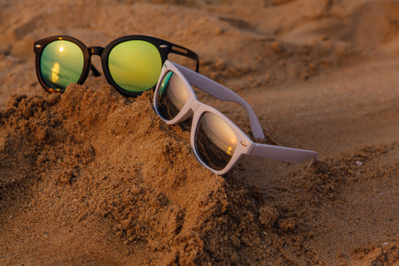 Sunglasses lying on sand with a reflection of sunset.