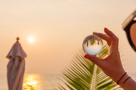 Crystal lens ball in hand with reflection of sea and sunset on the beach Stock Photo