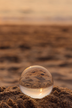 Crystal lens ball on the sand with reflection of sea and sunset on the beach