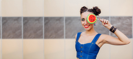 Bright makeup beautiful girl holding watermelon lollipop near the wall. Copy space.