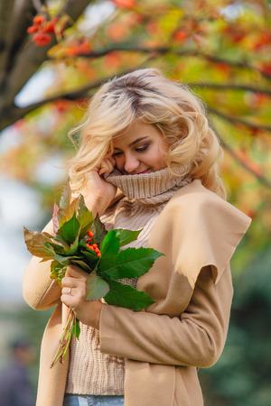 Beautiful elegant blonde woman dressed in a coat standing under the rowan tree holding bouquet of rowanberries and leaves in autumn park. Sunny october day.