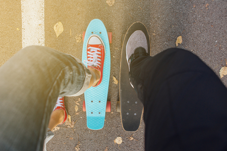 Close up of feet of a girl in red sneakers rides on blue penny skate board with pink wheels. Urban scene, city life. Sport, fitness lifestyle.