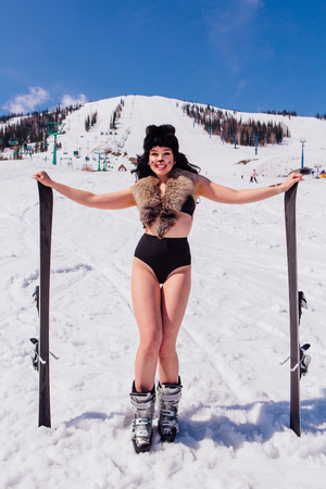 Attractive young woman dressed like cat woman with mountain ski on the slope
