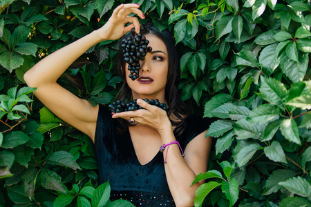 Portrait of young sexy brunette in black dress with black grapes. .