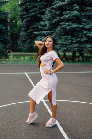 Charming brunette female dressed in a pink dress posing on the basketball court during sunset. Stock Photo
